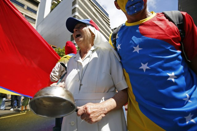 A nun hits an empty pot during a protest march against shortages of basic goods in Caracas January 24, 2015. (Photo by Jorge Silva/Reuters)