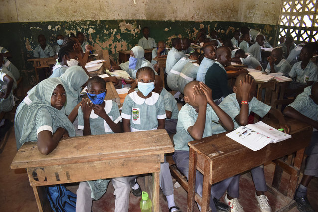 Pupils Concodia Primary school in Mombasa County, Kenya, Monday, January 4, 2021, as schools re-opened after a nine month break due to the COVID-19 pandemic. All Primary and secondary schools in the country were reopened in congested classes despite efforts by the national government to have fulfilled their promises of having new desks and new classes to avoid the social distance calamity which could cause the spread of the pandemic in schools. (Photo by Gideon Maundu/AP Photo)