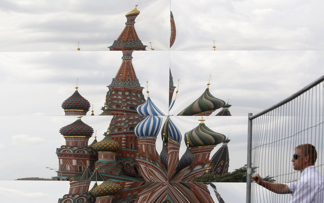 A reflection of St Basil's Cathedral is seen as a security guard opens a gate near a mirrored pavilion being built on Red Square in Moscow July 8, 2013. The structure is to be used for a one-off fashion show on Tuesday. (Photo by Sergei Karpukhin/Reuters)
