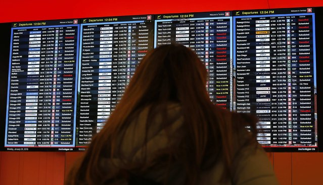A traveller looks at a list of departures at Logan Airport in Boston, Massachusetts January 26, 2015 ahead of a major winter storm predicted to hit the area later in the day. MassPort announced that no flights will depart Logan Airport after 7 pm. (Photo by Brian Snyder/Reuters)