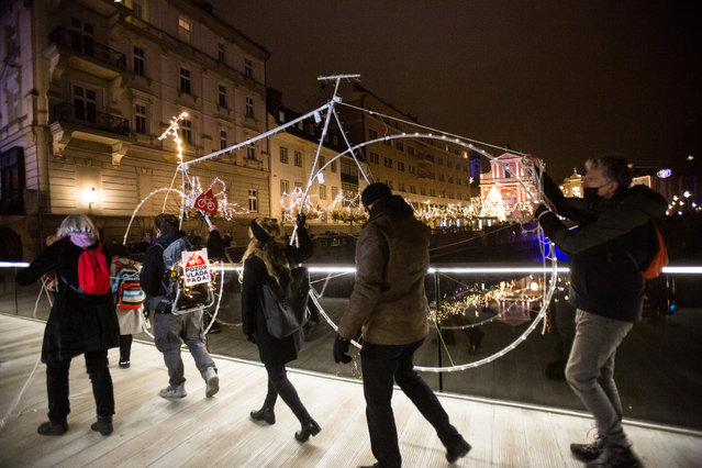Protesters carry a figure of a large bicycle decorated with lights as a symbol of anti-government protest to a bridge over Ljubljanica river in Ljubljana, Slovenia on December 18, 2020. Amid growing instability in the government of Janez Jansa, the anti-government protests in Ljubljana continued. On Friday, protesters strung up a lighted bicycle, a symbol of protests, over the Ljubljanica River in the city center and strolled through the streets carrying banners.  In order to respect the covid-19 epidemic restrictions that are subject to very big fines the protest was small, but creative. (Photo by Luka Dakskobler/SOPA Images/LightRocket via Getty Images)