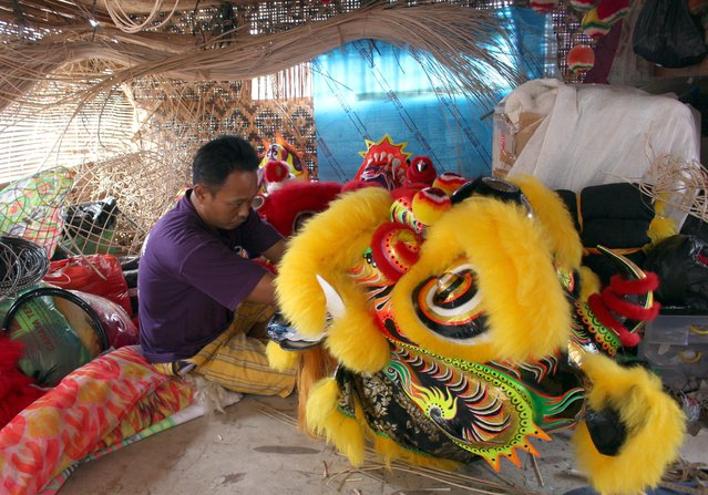 An Indonesian worker checks a barongsai (lion dance) mask for the upcoming Lunar New Year at  Lily Hambali's dragon and lion masks and custome maker in Bogor, Indonesia, 02 February 2015. (Photo by Adi Weda/EPA)