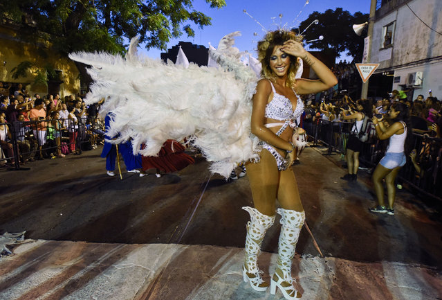 """A """"candombe"""" dancer wearing feathered wings performs at the """"Las Llamadas"""" parade during Carnival celebrations in Montevideo, Uruguay, Friday, February 6, 2015. (Photo by Matilde Campodonico/AP Photo)"""