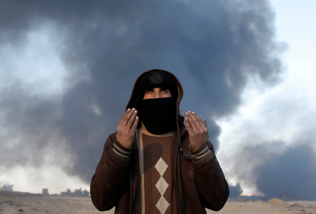 A man prays near oil field burned by Islamic State fighters in Qayyara, south of Mosul, Iraq November 23, 2016. (Photo by Goran Tomasevic/Reuters)