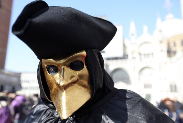 A masked reveller poses in front of Saint Mark's square during Carnival in Venice, February 8, 2015. (Photo by Stefano Rellandini/Reuters)