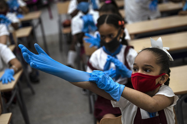A mask-wearing student puts on plastic gloves as a precaution amid the spread of the new coronavirus during class in Havana, Cuba, Monday, November 2, 2020. Tens of thousands of school children returned to class Monday in Havana for the first time since the coronavirus pandemic prompted authorities to shut the island down in April. (Photo by Ramon Espinosa/AP Photo)