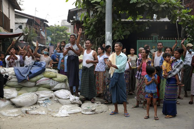 "Residents gesture with a three-fingers salute, a symbol of resistance, as the protesters marching past them in Mandalay, Myanmar, Friday, March 26, 2021. Protesters against last month's military takeover in Myanmar returned to the streets in large numbers Thursday, a day after staging a ""silence strike"" in which people were urged to stay home and businesses to close for the day. (Photo by AP Photo/Stringer)"