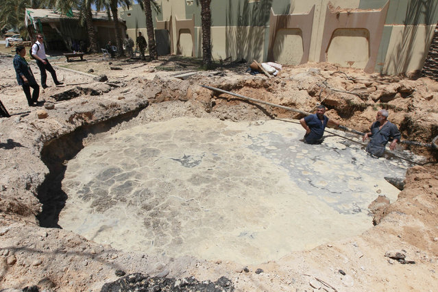 A crater, which the Libyan government said was caused by coalition air strikes, is seen at an area in Bab al-Aziziyah compound in Tripoli May 12, 2011. Libyan officials, who showed reporters around the scene of the air strike, at Gaddafi's Bab al-Aziziyah compound, said three people were killed and 25 wounded. (Photo by Louafi Larbi/Reuters)
