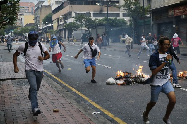 Opposition students run from police and past burning trash as they protest against President Nicolas Maduro's government in Caracas February 12, 2015. (Photo by Jorge Silva/Reuters)