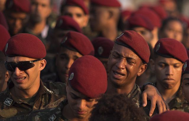 Soldiers cry as they leave the cemetery after attending the burial of soldier Joao Viktor da Silva in Japeri, Brazil, Tuesday, August 21, 2018. Da Silva died during shootouts with military personnel and police in greater Rio de Janeiro on Monday as violence erupted in several areas of the city. (Photo by Leo Correa/AP Photo)