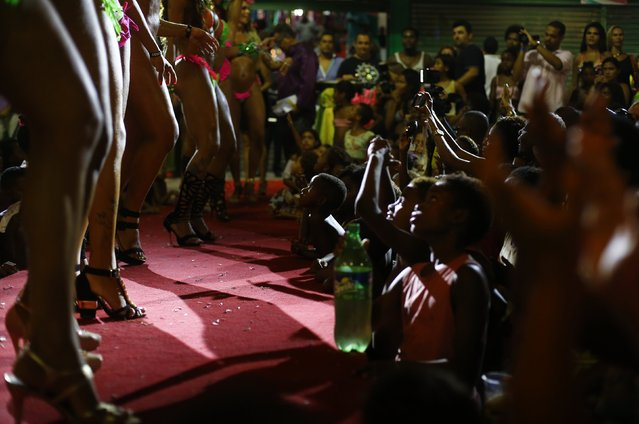 Residents of Mangueira slum watch as participants attend a beauty contest for transvestites and transsexuals at the entrance of the Glam Gay pre-carnival Ball, in Mangueira samba school in Rio de Janeiro February 11, 2015. (Photo by Ricardo Moraes/Reuters)