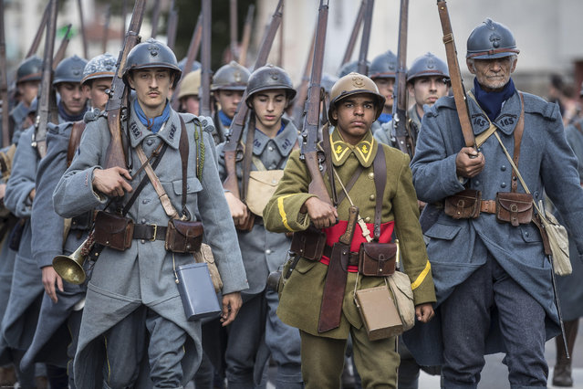 Men dressed in WWI uniforms march during a parade, part of a reconstruction of the WWI battle of Verdun, Saturday, August 25, 2018, in Verdun, eastern France.  Hundreds of volunteers from 18 countries gathered in the French town Verdun as part of a string of events to mark the centenary of the end of World War One, with re-enactors dressed in period soldiers' uniforms bringing to life a big military encampment in the town. (Photo by Jean-Francois Badias/AP Photo)