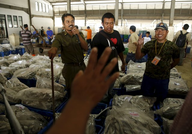 A customer raises his hand to buy fish at Muara Angke fish auction in Jakarta, January 4, 2016. (Photo by Reuters/Beawiharta)