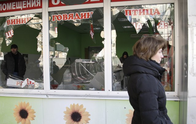 A woman walks past a grocery store damaged by a recent shelling in central Donetsk, eastern Ukraine February 14, 2015. (Photo by Alexander Ermochenko/Reuters)