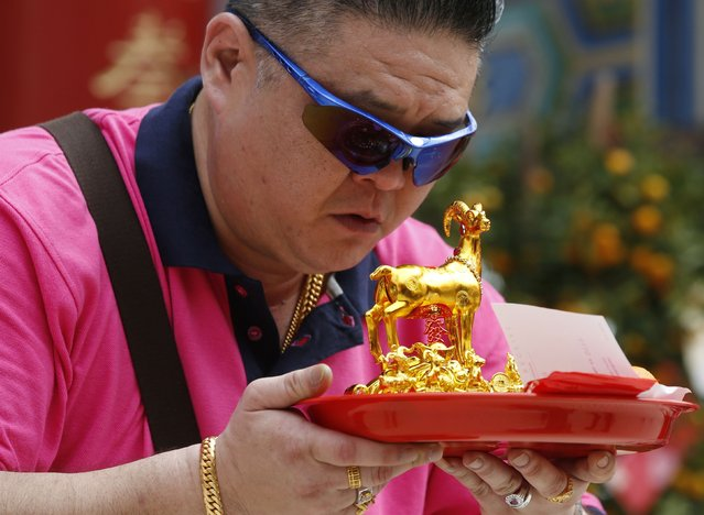 A man bows his head in prayer at the Thean Hou temple on Chinese New Year in Kuala Lumpur, February 19, 2015. (Photo by Olivia Harris/Reuters)
