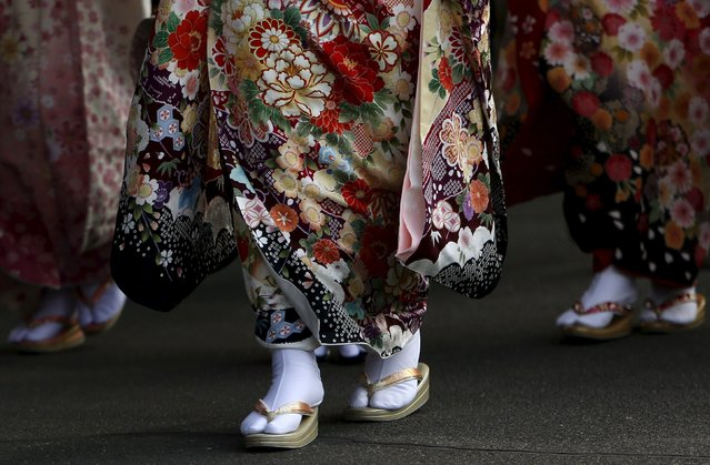 Japanese women wearing kimonos walk before their Coming of Age Day celebration ceremony at an amusement park in Tokyo January 11, 2016. (Photo by Yuya Shino/Reuters)