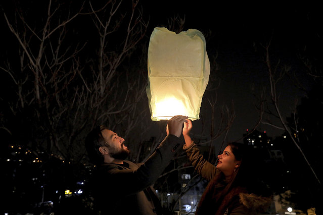 """People fly a wishing lantern ahead of the Persian New Year, or Nowruz, meaning """"New Day"""" in Tehran, Iran, Monday, March 15, 2021. (Photo by Ebrahim Noroozi/AP Photo)"""