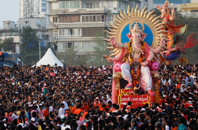 Devotees pull an idol of Hindu elephant god Ganesh, the deity of prosperity, as it is carried for immersion into the Arabian Sea on the last day of the Ganesh Chaturthi festival in Mumbai, September 23, 2018. (Photo by Danish Siddiqui/Reuters)