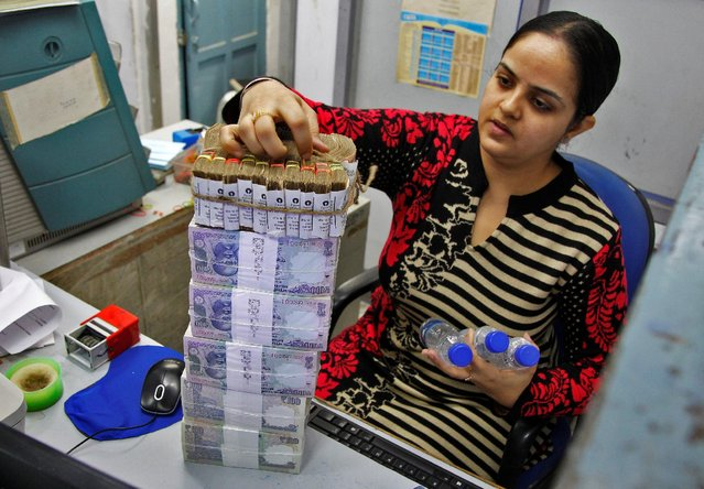 A cashier stacks Indian currency notes inside a bank in Chandigarh, India, November 19, 2016. (Photo by Ajay Verma/Reuters)