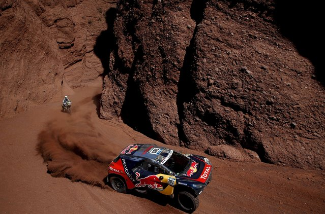 Carlos Sainz of Spain drives his Peugeot past Hans Smit of Netherlands on his Husqvarna motorcycle during the eighth stage in the Dakar Rally 2016 near Cafayate, Argentina, January 11, 2016. (Photo by Marcos Brindicci/Reuters)
