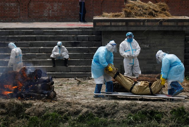Men wearing personal protective equipment (PPE) prepare the body of a COVID-19 victim for cremation on the bank of Bagmati River, as the number of deaths increases amid the spread of the coronavirus disease (COVID-19) in Kathmandu, Nepal on May 3, 2021. (Photo by Navesh Chitrakar/Reuters)