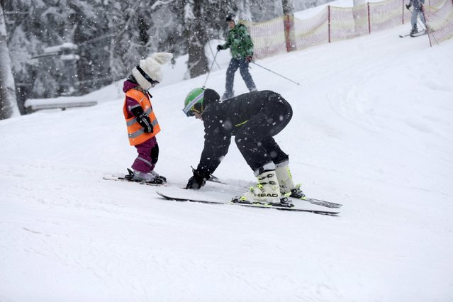 A man teaches a child alpine skiing during World Snow Day event in Sigulda, Latvia, January 17, 2016. (Photo by Ints Kalnins/Reuters)