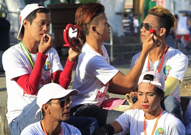 Members of the gay community, hired as traffic enforcers, put on make-up before heading to their posts along a busy street in Rosario town, Cavite city, south of Manila February 24, 2015. The Rosario government earlier in the month hired 20 members of the local gay community as traffic wardens at busy intersections, with traffic controlling duties frequently accompanied by dance routines, local media reported. (Photo by Romeo Ranoco/Reuters)
