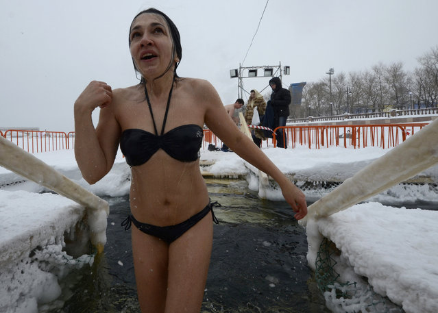A woman makes a cross sign after taking a dip in icy waters during celebrations for the Orthodox Epiphany in the Sea of Japan in the far eastern city of Vladivostok, Russia, January 19, 2016. Orthodox believers mark Epiphany on January 19 by immersing themselves in icy waters regardless of the weather. (Photo by Yuri Maltsev/Reuters)