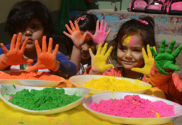 Indian children from the Bright Academy pose with colored powder known as gulal used during the Holi festival in Siliguri  on March 4, 2015.   'Holi', the festival of colours, is a riotous celebration of the coming of spring and falls on the day after full moon annually in March. Revellers spray coloured powder and water on each other with great gusto, whilst adults extend the hand of peace.   AFP PHOTO / Diptendu DUTTA        (Photo credit should read DIPTENDU DUTTA/AFP/Getty Images)