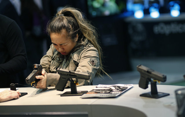 A woman looks at a handgun at the Glock booth at the Shooting Hunting and Outdoor Trade Show, Tuesday, January 19, 2016, in Las Vegas. (Photo by John Locher/AP Photo)