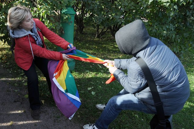 A gay rights activist (L) fights for her rainbow flag against an anti-gay protester during a gay pride event in Saint Petersburg, Russia, on Oktober 13, 2013. (Photo by Olga Maltseva/AFP Photo)