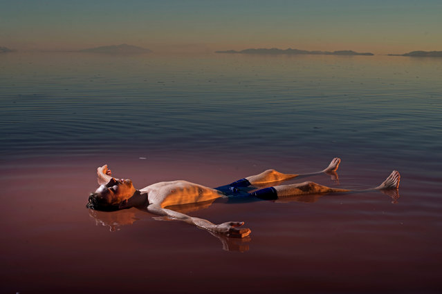 """Great Salt Lake, Utah, 2016, by Carolyn Drake. """"The north arm of Utah's Great Salt Lake stopped receiving fresh water over 50 years ago, when the Railroad built a causeway that split it in two, making the upper half incredibly saline, a haven for a red-algae called Dunaliella salina. A couple of months after I was there, a bridge was constructed allowing the water in the upper portion of the lake to mix with the fresher water in the lower lake, where another species of algae tints the water green. It is a picture of man in nature that feels strikingly unnatural; the natural order is askew"""". (Photo by Carolyn Drake/Magnum Photos)"""