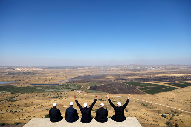 Israeli Druzes sit together watching the Syrian side of the Israel-Syria border on the Israeli-occupied Golan Heights, Israel July 7, 2018. (Photo by Ronen Zvulun/Reuters)