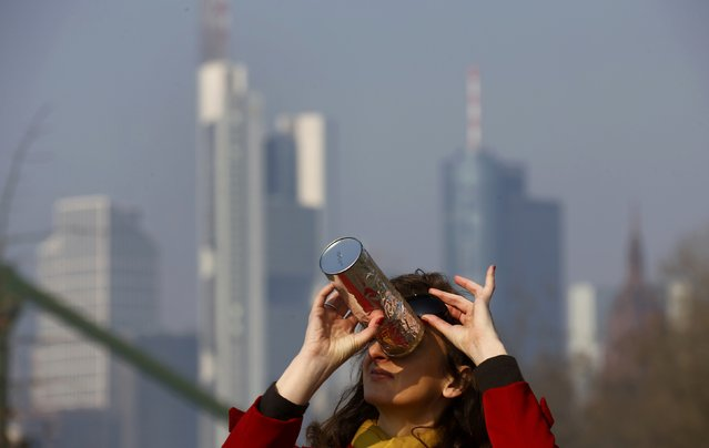 Irena Simic uses a self-made monocular to watch a partial solar eclipse on the bank of river Main in front of the skyline of Frankfurt, March 20, 2015. (Photo by Kai Pfaffenbach/Reuters)