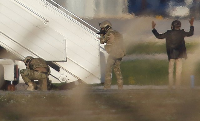 Two hijackers of a Libyan Afriqiyah Airways Airbus A320 surrender to Maltese military on the runway at Malta Airport, December 23, 2016. (Photo by Darrin Zammit-Lupi/Reuters)