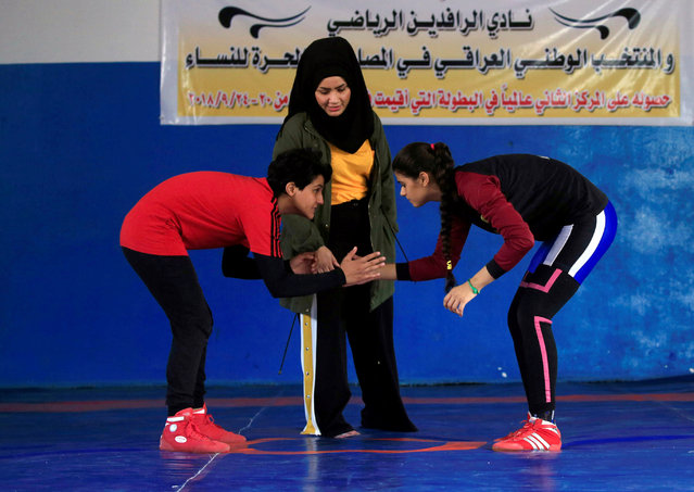 Iraqi women, part of the country's first women's wrestling squad, face each other during practice at the sports club in Diwaniya, Iraq on November 10, 2018. On the blue mats of the al-Rafideen Club in the conservative city of Diwaniya, some 180 km (110 miles) south of Baghdad, some 30 female wrestlers, some still wearing headscarves, train three times a week. When a big competition comes up, they train every day. (Photo by Alaa Al-Marjani/Reuters)
