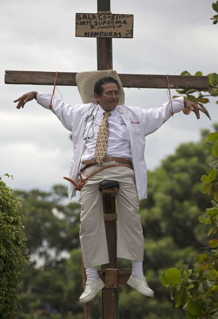 Francisco Pagoada hangs from a cross, with some support, as part of his protest against the Supreme Court that denied Pagoada's request to run as an independent candidate for mayor, in Tegucigalpa, Honduras, Wednesday, November 20, 2013. Honduras will hold general elections on Sunday. (Photo by Eduardo Verdugo/AP Photo)