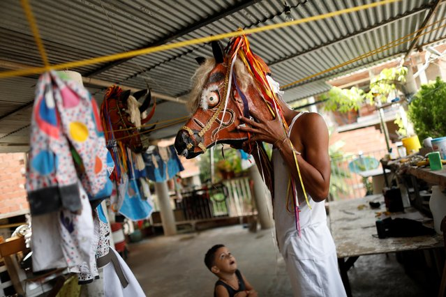 """A member of Venezuelan brotherhood """"Dancing Devils"""" wears a horse mask while his nephew looks at him during their annual Corpus Christi celebration with a call for the end of the coronavirus disease (COVID-19), in Naiguata, Venezuela on June 3, 2021. (Photo by Leonardo Fernandez Viloria/Reuters)"""