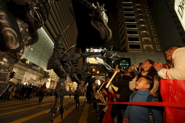 """Spectators react to stilt walkers """"The Dinosaurs"""" from the Netherlands during a Lunar New Year parade in Hong Kong, China February 8, 2016 to celebrate the first day of the Lunar New Year of the Monkey. (Photo by Bobby Yip/Reuters)"""