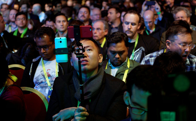 A showgoer uses two smartphones before the Nvidia keynote address at CES in Las Vegas, January 4, 2017. (Photo by Rick Wilking/Reuters)