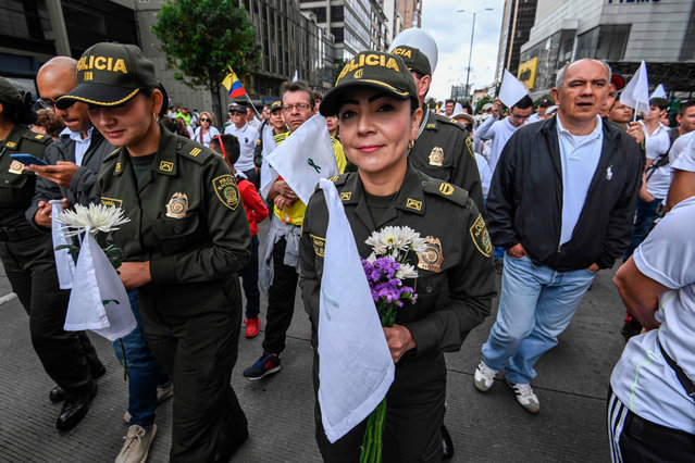 Colombian police officers take part in a march against terrorism, in repudiation of the police academy recent car bombing that left 20 people dead, and in support of the victims and their relatives, on January 20, 2019. The Colombian government on Friday blamed leftist ELN rebels for Thursday's bombing of a police academy in Bogota that killed 20 people as well as the attacker, and dealt a body blow to the peace process. President Ivan Duque reinstated arrest warrants for 10 ELN peace negotiators who are part of the guerrilla group's delegation to the Cuba talks. (Photo by Juan Barreto/AFP Photo)