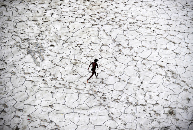 An Indian street child plays in a dry river bed after flood waters receded in Allahabad  on October 25, 2013. (Photo by Sanjay Kanojia/AFP Photo)