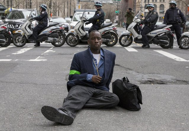 "A demonstrator sits on the roadway during a protest against police brutality against minorities,  in New York April 14, 2015. Protesters angered by fresh cases of police violence against unarmed black men in the United States gathered on Tuesday in New York City in a protest organized by the group ""Stop Mass Incarceration Network"" hoping to invigorate a national discussion on the thorny issue. (Photo by Brendan McDermid/Reuters)"
