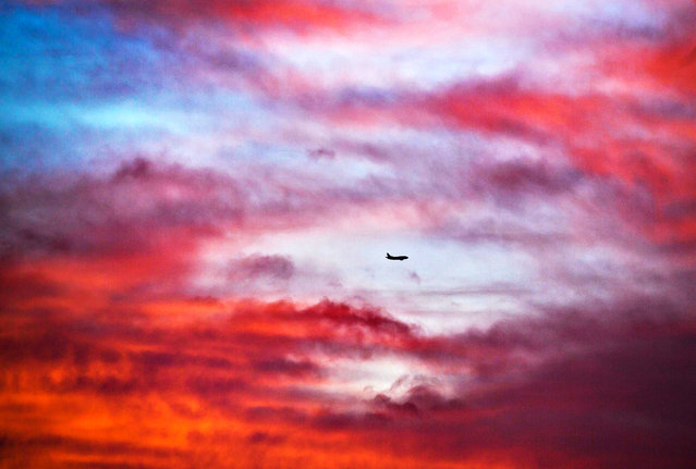 An aircraft approaches the airport while the clouds are turned red by the rising sun in Frankfurt Main, Germany, on January 3, 2014. (Photo by Rank Rumpenhorst/AFP Photo/DPA)