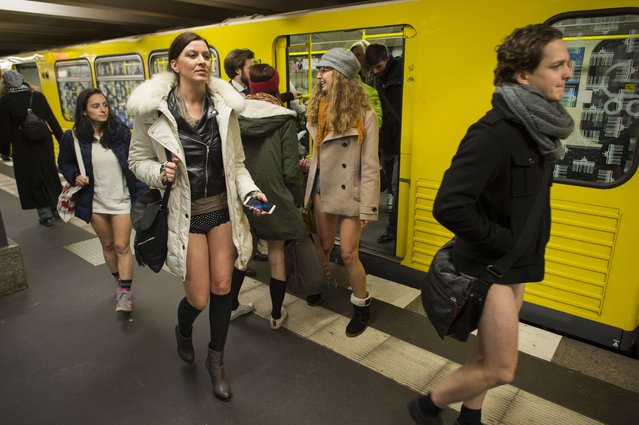 """People taking part in the """"No Pants Subway Ride"""" exit a train on the U2 Subway line in Berlin on January 12, 2014. (Photo by Odd Andersen/AFP Photo)"""