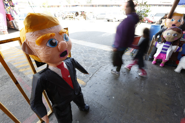 """People pass a pinata in the image of Republican presidential candidate Donald Trump Wednesday, March 2, 2016, in Tijuana, Mexico. Former Mexican President Vicente Fox on Wednesday stood by his comparison of Donald Trump to Adolf Hitler, saying the Republican presidential front-runner """"believes in the white supremacy."""" Fox is calling on Americans to """"wake up"""" from """"this Republican nightmare"""". (Photo by Gregory Bull/AP Photo)"""