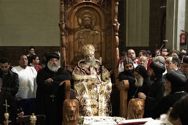 Egyptian Coptic priests gather around the body of Pope Shenuda III, the spiritual leader of the Middle East's largest Christian minority, sitting dressed in formal robes on a wooden throne at the Saint Mark's Coptic Cathedral in Cairo's al-Abbassiya district on March 19, 2012. (Photo by Gianluigi Guercia/AFP Photo)