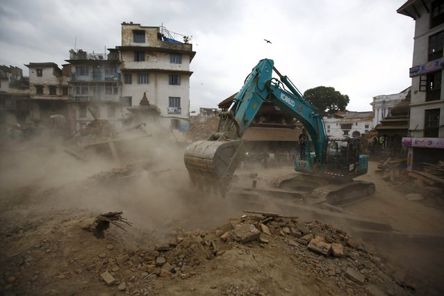 An excavator digs the rubble to search for the bodies after an earthquake hit, in Kathmandu, Nepal April 25, 2015. (Photo by Navesh Chitrakar/Reuters)