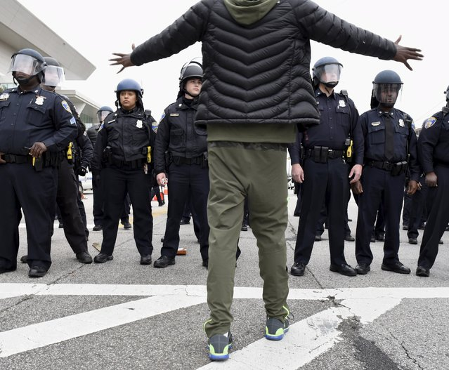 A demonstrator gestures towards a line of police near Camden Yards during a protest against the death in police custody of Freddie Gray in Baltimore April 25, 2015. (Photo by Sait Serkan Gurbuz/Reuters)