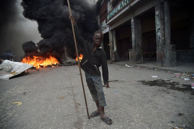 A boy stands before burning tires on the fourth day of protests in Port-au-Prince, on February 10, 2019. Demonstrators are demanding the resignation of Haitian President Jovenel Moise, and protesting the Petrocaribe fund which investigations concluded nearly $2 billion from the program was misused. (Photo by Hector Retamal/AFP Photo)
